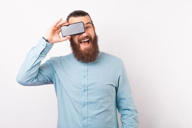 Веселый бородатый мужчина в непринужденной обстановке держит смартфон над глазами и улыбается
