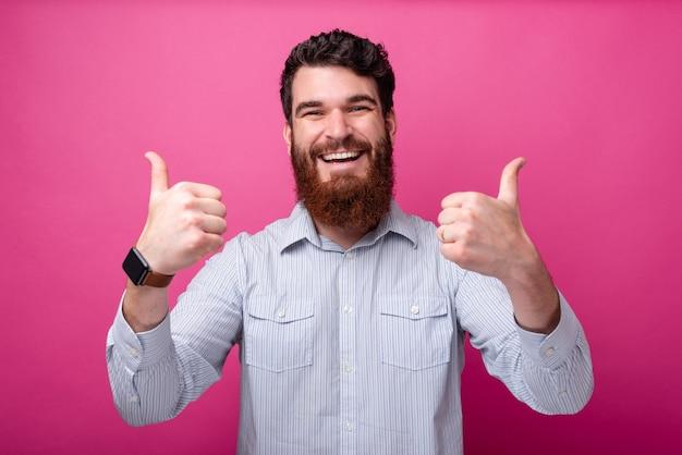 親指を立てるジェスチャーをカジュアルに見せて陽気なひげを生やした男
