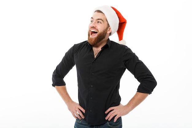 腰に腕を保持しているクリスマスの帽子の陽気なひげを生やした男