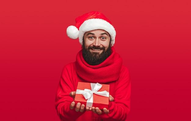 Веселый бородатый мужчина в новогодней шапке предлагает упакованную подарочную коробку