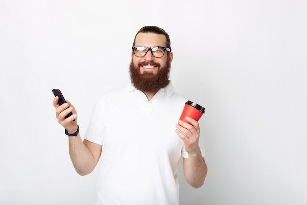 Веселый бородатый мужчина в белой футболке использует смартфон и держит чашку кофе с собой