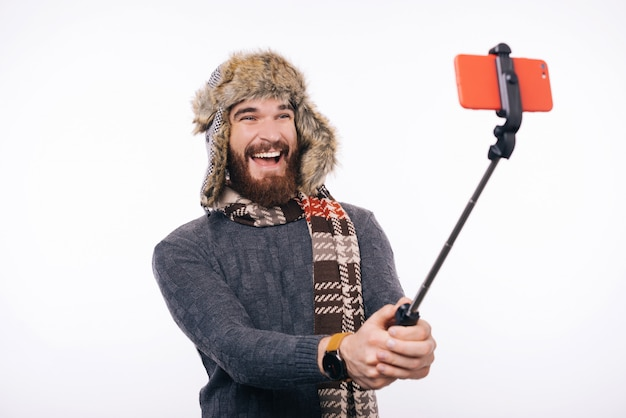Cheerful bearded man is making a photo with selfie stick. he is wearing winter accessories.