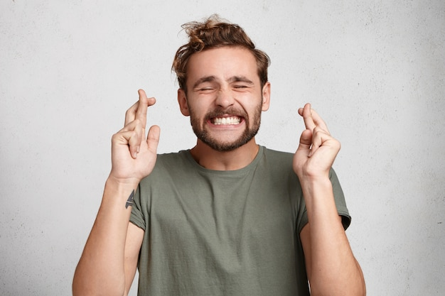 Cheerful bearded man keeps fingers crossed, smiles broadly and closes eyes