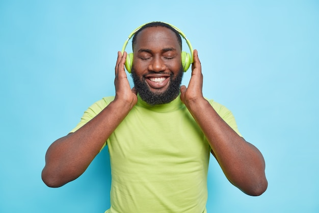 Cheerful bearded man keeps hands on headphones smiles gladfully keeps eyes closed enjoys favorite music dressed in green t shirt isolated over blue wall
