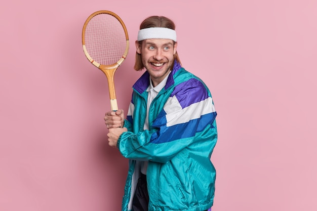 Cheerful bearded man player holds tennis racket enjoys active game on court dressed in activewear has happy expression looks into distance.