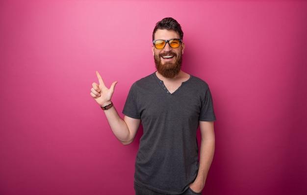 ピンクの背景の上に、指で上向きの陽気なひげを生やした男