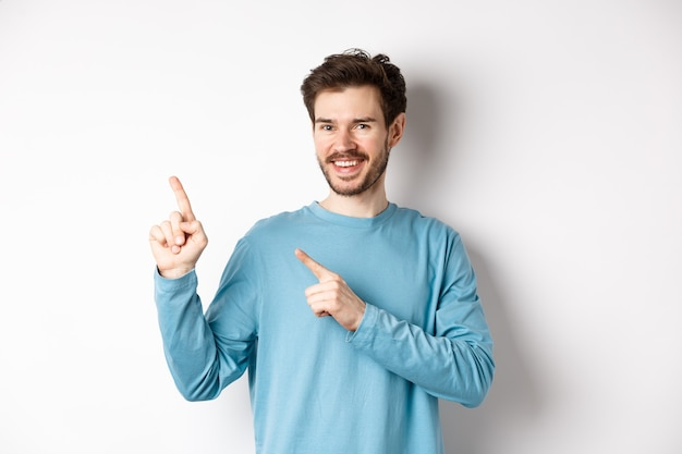 Cheerful bearded man showing advertisement on copy space, pointing fingers at upper left corner logo and smiling, standing over white background.