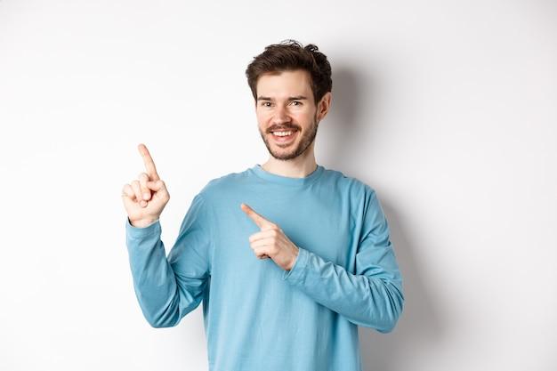 쾌활 한 수염 난된 남자 복사 공간에 광고를 게재, 왼쪽 상단 모서리 로고에서 손가락을 가리키고 웃 고, 흰색 배경 위에 서.