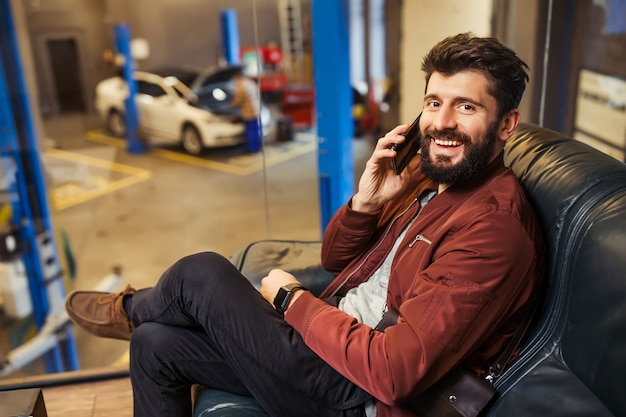 Cheerful bearded man sitting in waiting room of car service center talking on the smartphone and looking at the camera