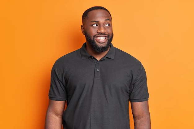 Cheerful bearded man smiles toothily has white perfet teeth looks aside with interest wears casual black t shirt poses against vivid orange wall
