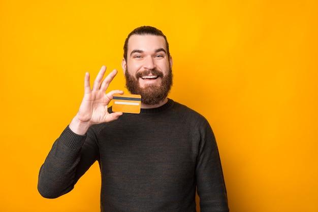 밝은 수염 된 남자 웃 고 노란색 이상 신용 카드를 보여주는