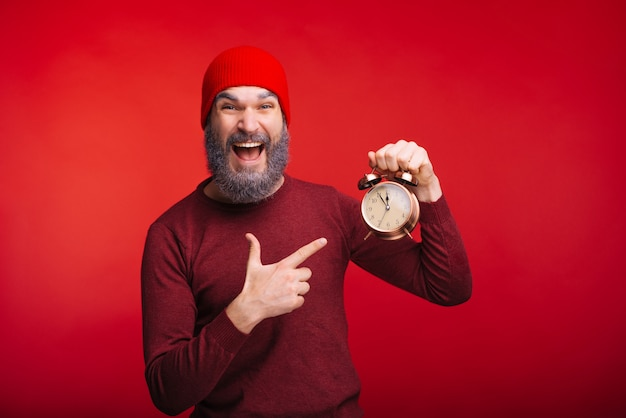 Веселый бородатый человек, стоящий над красным пространством, указывая на будильник