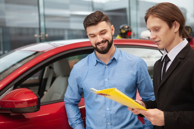 Cheerful bearded man talking to car dealer, buying new automobile at the dealership, copy space