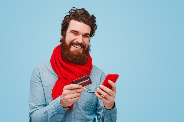 Cheerful bearded man using smartphone for online shopping