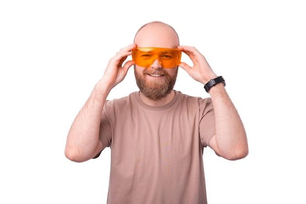 Cheerful bearded man wearing big yellow eyeglasses on white