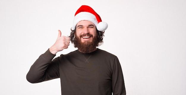 サンタクロースの帽子をかぶって親指を立てて元気なひげを生やした男