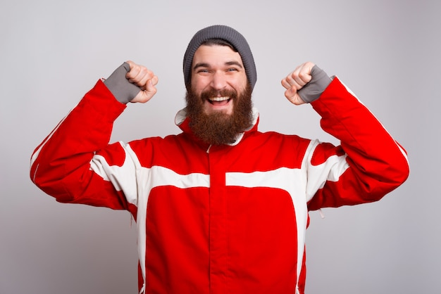 Cheerful bearded man in winter clothes celebrate
