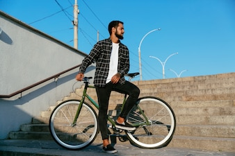 Cheerful bearded man with bicycle, standing on steps, near underground crossing