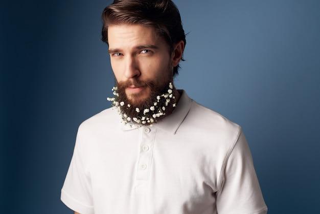 彼の髪のモダンなスタイルの花を持つ陽気なひげを生やした男