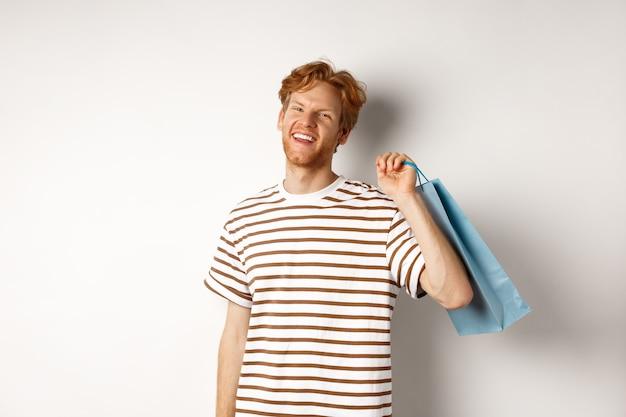 쇼핑을 즐기고, 어깨에 가방을 들고 웃고, 흰색 배경 위에 서 있는 빨간 머리를 가진 쾌활한 수염 난 남자