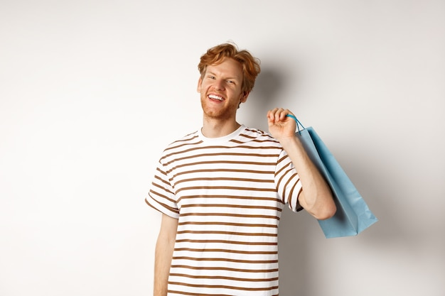 Cheerful bearded man with red hair enjoying shopping, holding bag over shoulder and smiling, standing over white background.