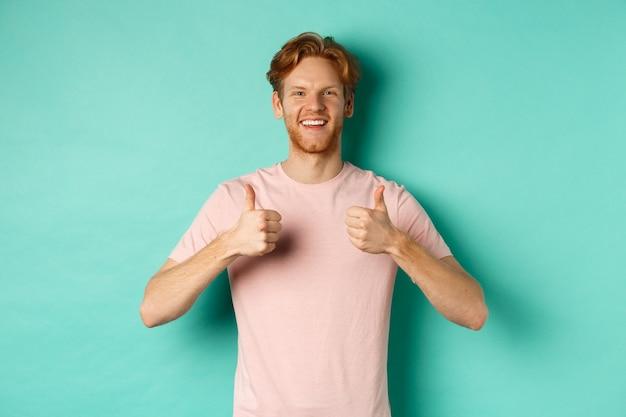 ターコイズブルーの背景に立って、何かを好きで承認し、プロモーションを賞賛し、親指を立てて示す赤い髪の陽気なひげを生やした男