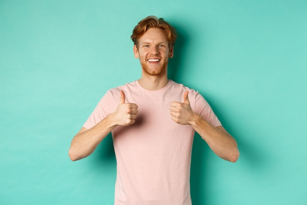 Cheerful bearded man with red hair showing thumbs-up, like and approve something, praising promo, standing against turquoise background.