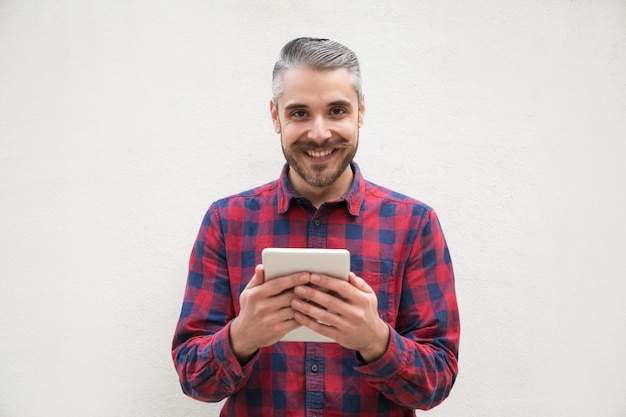 Cheerful bearded man with tablet pc