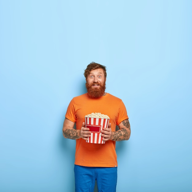 Cheerful bearded redhead man eats popcorn