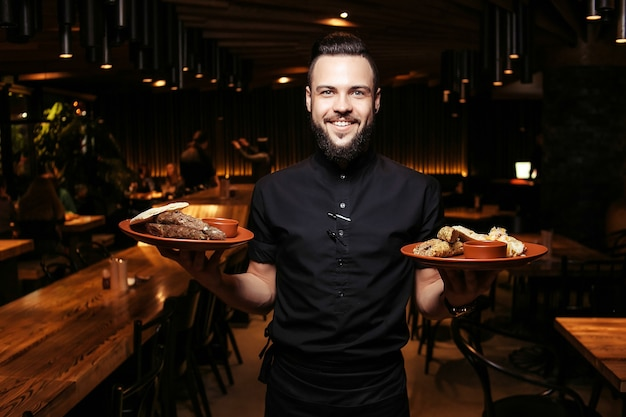 Cheerful bearded waiter with kebab, barbecue and side dish in a georgian restaurant