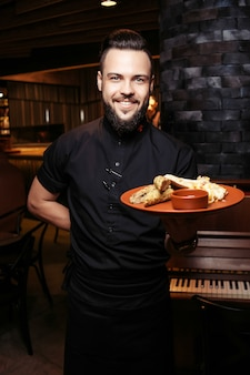 Cheerful bearded waiter with kebab, barbecue and side dish in a georgian restaurant.