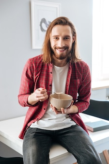 Cheerful bearded young man eating breakfast at home