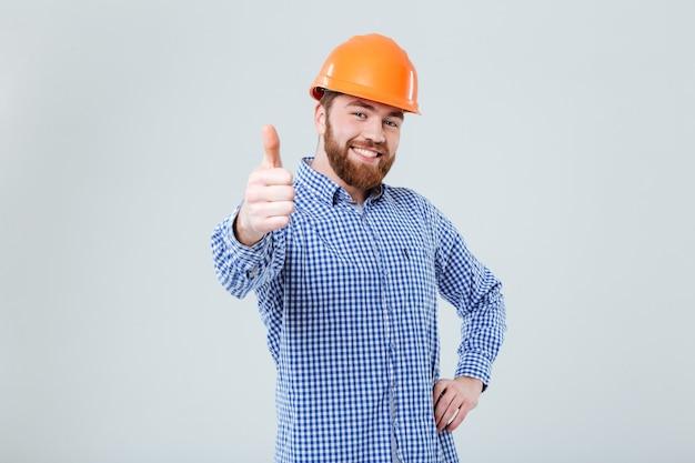 Веселый бородатый молодой человек в шлеме стоит и показывает палец вверх над белой стеной