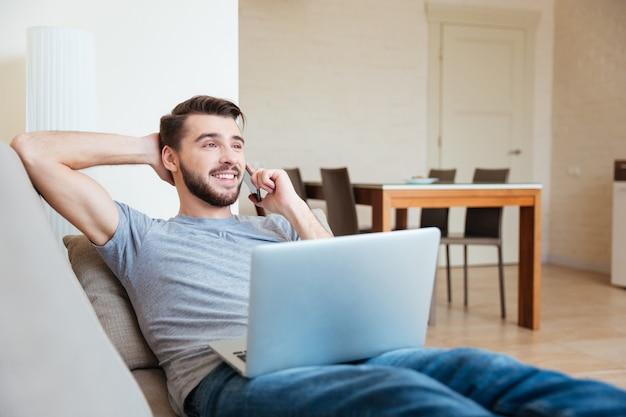 Веселый бородатый молодой человек лежит на диване с ноутбуком и разговаривает по мобильному телефону дома