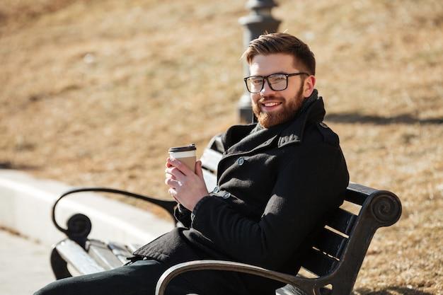 陽気なひげを生やした若い男がベンチに座ってコーヒーを飲む