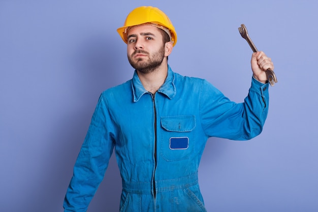 Cheerful bearded young man wearing yellow helmet holding wrench tool in hand and looking direcly at camera, looking with anger, wants to hit somebody with his instrument. people emotions concept.