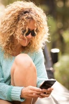 陽気な美しい大人の白人女性は、屋外のレジャー活動だけで電話接続をエノジーします-ローミング通信活動を持つ人々と現代の技術