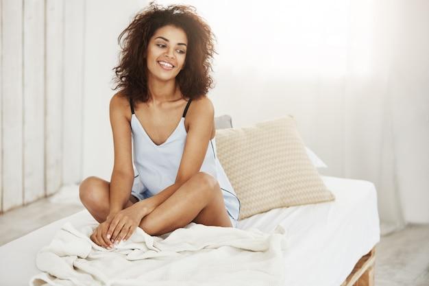 朝ベッドに座って笑っているパジャマで陽気な美しいアフリカ人女性。