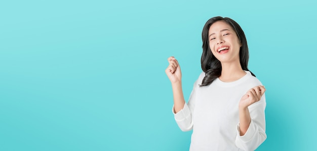 Cheerful beautiful asian woman in casual white t-shirt and happy face smile on blue background