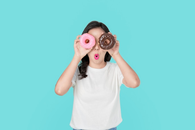 Cheerful beautiful asian woman covering her eyes with colorful donuts on blue background.