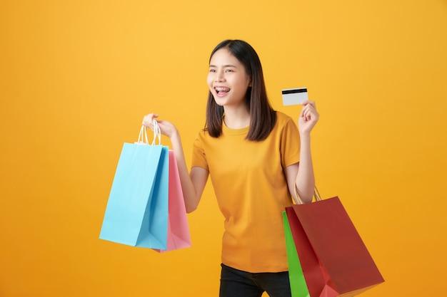 Жизнерадостная красивая азиатская женщина держа multi покрашенные хозяйственные сумки и кредитную карточку