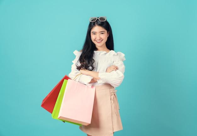 Веселая красивая азиатская женщина, держащая разноцветные сумки и скрещенные руки