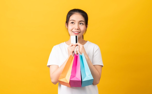 Cheerful beautiful asian woman holding multi coloured shopping bags and credit card on orange background.