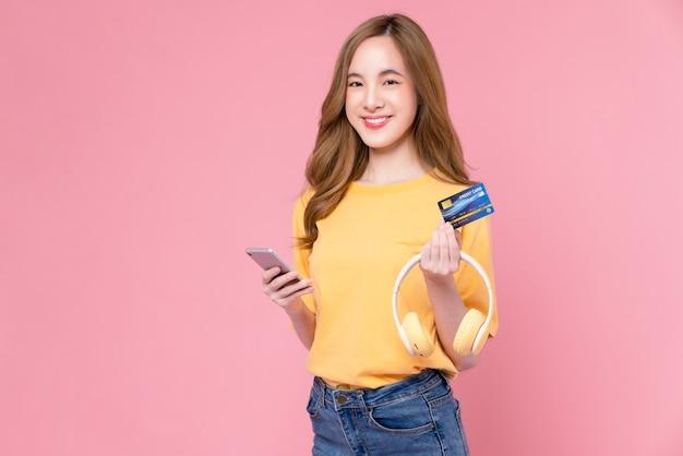Веселая красивая азиатская женщина, держащая смартфон и кредитную карту макета, наушники на розовом фоне.