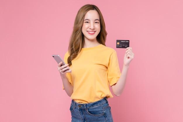Веселая красивая азиатская женщина, держащая смартфон и кредитную карту макета на розовом фоне.