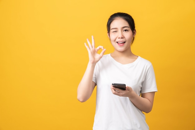 スマートフォンを保持し、明るい黄色の背景にokサインを示す陽気な美しいアジアの女性。