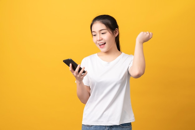 Cheerful beautiful asian woman holding smartphone on light yellow wall.