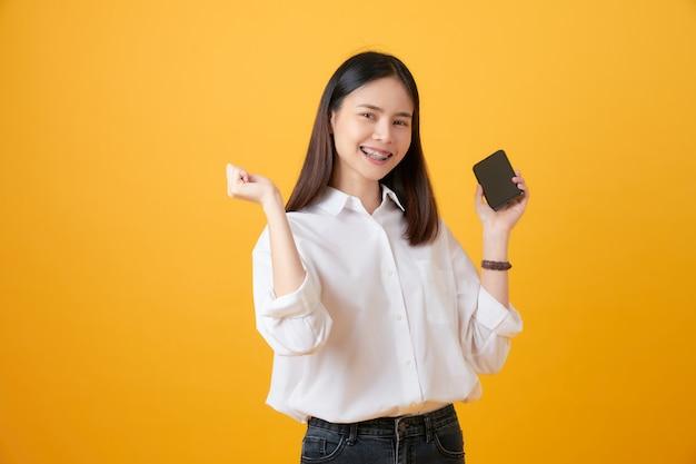 明るい黄色の背景にスマートフォンを保持している陽気な美しいアジアの女性