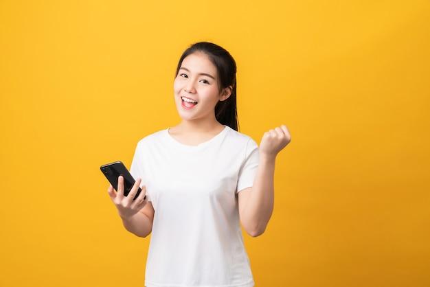 明るい黄色の背景にスマートフォンを保持している陽気な美しいアジアの女性。