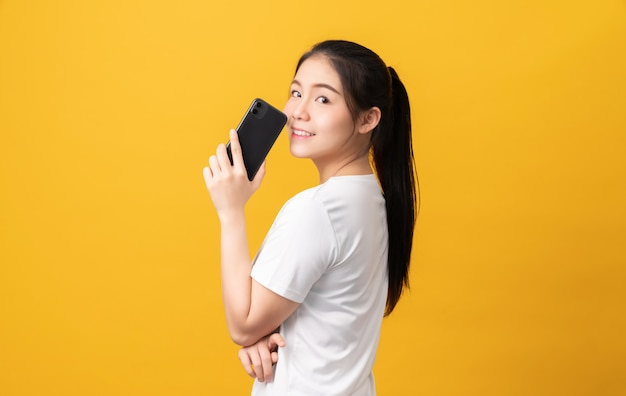 Cheerful beautiful asian woman holding smartphone and typing message on light yellow background